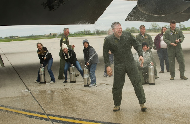 Lt. Col. Jason Karren, 5th Bomb Wing chief of wing inspections, is sprayed with water by his children after his final B-52 flight at Minot Air Force Base, N.D., May 12, 2016. With his retirement approaching, Karren's family and friends celebrated his last flight as an Air Force pilot. (U.S. Air Force photo/Senior Airman Apryl Hall)