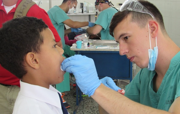 U. S. Army Spc. Tyler Novich, Joint Task Force-Bravo Medical Element dental specialist, cares for a pediatric patient after a molar extraction in the Catholic University, Tegucigalpa, Honduras, May 6, 2016. A total of 208 pediatric patients between the ages of 2 and 16 were seen during the two-week mission in the Honduran capital. (U.S. Army photo by 1st Lt. Jenniffer Rodriguez)