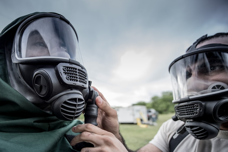 1st Lt. Lenton Johnson, 149th Force Support Squadron, Texas Air National Guard, headquartered at Join Base San Antonio-Lackland, waits while Tech. Sgt. Edwin Bello, also 149th FSS, adjusts his chemical protective mask at JBSA-Lackland, Texas, April 10, 2016. These airmen are members of the 149th FSS Fatality Search and Recovery Team. These FSRT members are training on how to move into a contaminated area and recover remains after a chemical disaster. (U.S. Air National Guard photo by Tech. Sgt. Eric L. Wilson)