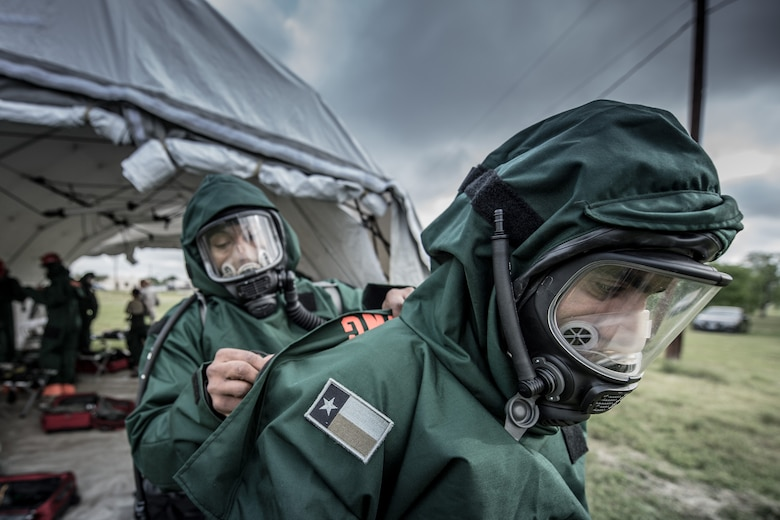 1st Lt. Lenton Johnson helps Tech. Sgt. Edwin Bello secure his chemical protective suit at Joint Base San Antonio, Texas, April 10, 2016. These airmen are members of the 149th Force Support Squadron, Fatality Search and Recovery Team. Members of the FSRT are training on how to move into a contaminated area and recover remains after a chemical disaster. (U.S. Air National Guard photo by Tech. Sgt. Eric L. Wilson)