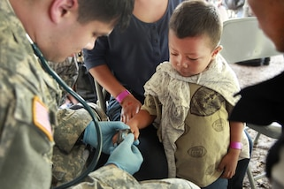 Army Spc. Joshua Towne, left, checks a patient's heart rate during Beyond the Horizon 2016 in San Padro, Guatemala, May 16, 2016. Towne is assigned to the 396th Combat Support Hospital Company. Army photo by Spc. Kelson Brooks