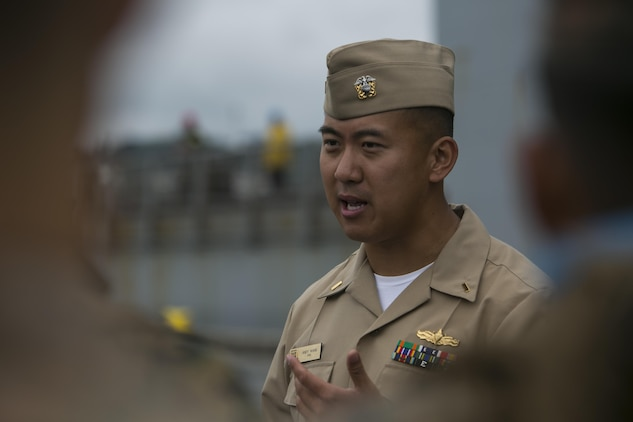 Navy Ensign Andy Wang explains naval traditions, rules and regulations to Marines and Sailors of Task Force Koa Moana before they board the USNS Sacagawea (T-AKE 2) for a series of bilateral, multinational exercises at Tengan Pier, Okinawa, Japan, May 17, 2016. The series of exercises provide basic military training and the opportunity to exchange engineering and infantry tactics between participating nations to increase interoperability and to preserve peace in the Asia-Pacific region. Wang, from Canton, Mich., is the liaison officer for USNS Sacagawea. His job is to provide a link between the ship's staff and the service members aboard. (U.S. Marine Corps photo by Cpl. William Hester/ Released)