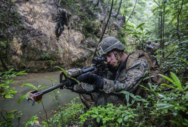 U.S. Marine Lance Cpl. Justin D. Enger sets up a security perimeter while the rest of his platoon rappels down the mountain at the Jungle Warefare Training Center, May 19, 2016 at Camp Gonsalves, Okinawa, Japan. Enger is a combat engineer with 9th Engineer Support Battalion, 3rd Marine Logistics Group, III Marine Expeditionary Force. Enger and his platoon attended the 5-day Course at JWTC. The course gives Marines the skills to shoot, move and communicate within a jungle environment. (U.S. Marine Corps photo by Lance Cpl. Jessica N. Etheridge/Released)