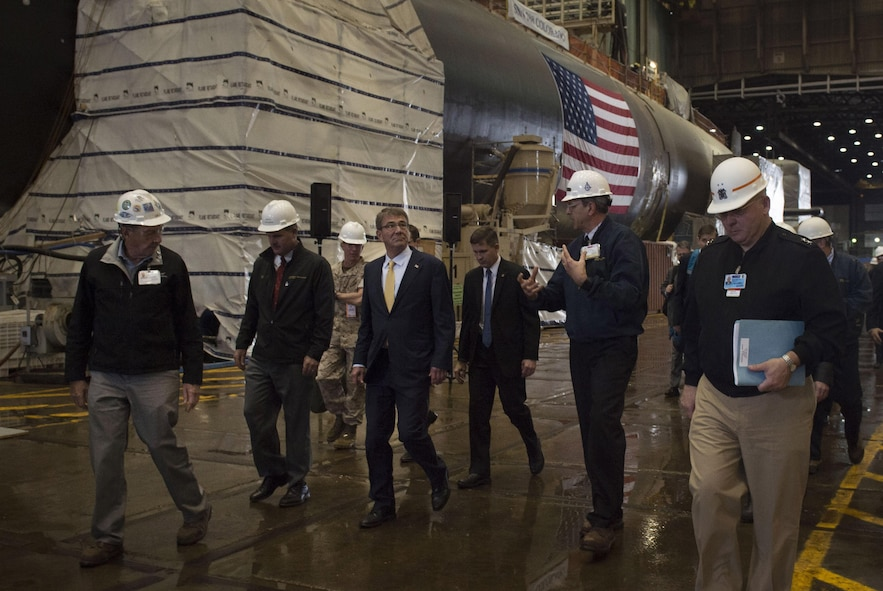 Defense Secretary Ash Carter walking with executives.
