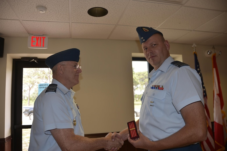Royal Canadian Air Forces LCol Larry Weir, outgoing Canadian Detachment Commander, congratulates Royal Canadian Air Forces Maj David Kruger, Continental U.S. Aerospace Defense Region-1st Air Force (Air Forces Northern) Intelligence Directorate, after presenting him with the Canadian Forces' Decoration Clasp, prior to the Canadian Detachment Change of Command Ceremony May 18. The decoration is awarded to members of the Canadian Forces of all ranks who have completed 12 years of service with a record of good conduct. A clasp is awarded for every subsequent 10 years designated by a silver rosette. (Air Force Photo released/Mary McHale)