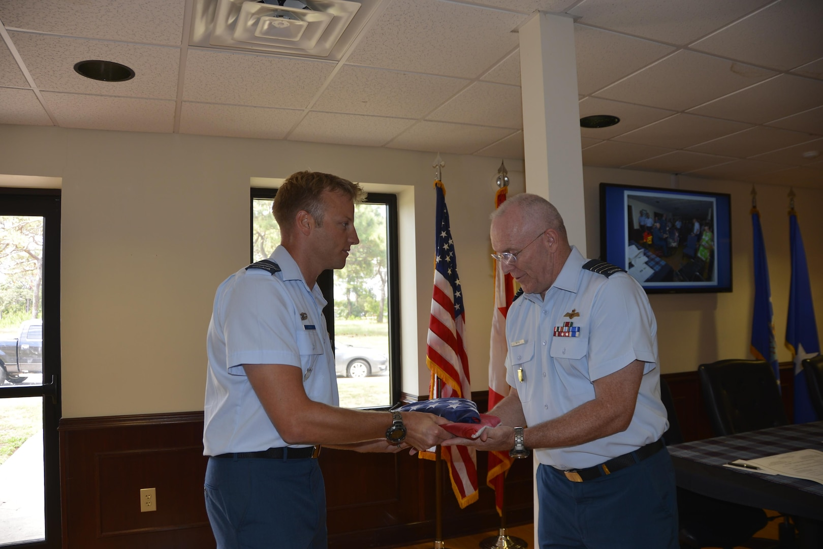 Royal Canadian Air Force Maj Reid Surkan, Continental U.S. Aerospace Defense Region-1st Air Force (Air Forces Northern) Plans, Policy and International Military Affairs Directorate, presents folded Canadian and American flags to LCol Larry Weir, in recognition of Weir's honorable tenure as Canadian Detachment Commander during a change of command ceremony here May 18. During the ceremony, Weir relinquished command to LCol Brian Murray. (Air Force Photo released/Mary McHale)