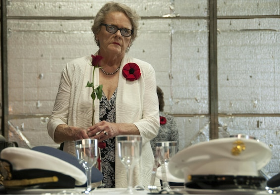 A member of the American Legion Auxillary 626 approaches a table set for those who never came home from war with a red rose, during the Vietnam War Veterans Recognition Ceremony at Naval Air Station Fort Worth Joint Reserve Base, Texas, April 22. The flower serves as a reminder of service members who are or were missing and those who are still waiting and seeking answers. (U.S. Air Force photo by Staff Sgt. Melissa Harvey)