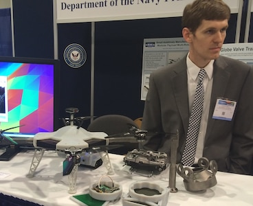 """NATIONAL HARBOR, Md. (May 17, 2016) - Navy engineer Steve Price briefs 2016 Sea-Air-Space Expo attendees on the small additively manufactured modular payload multi-rotor. This low cost, 3D printed, unmanned aerial vehicle can accept a wide variety of custom payloads. The UAV was one of the exhibits featured at the Navy Additive Manufacturing Showcase in Dahlgren, Va., last month that were selected for display at the Sea-Air-Space Expo. """"The volume of creative and innovative ideas made feasible with 3D Printing is astounding,"""" said Lynn Shoppell, a Naval Surface Warfare Center Dahlgren Division physicist after the Dahlgren showcase. """"The exhibitors demonstrated that their concepts for increased technical capabilities, rapid prototyping, improved logistics operations, and cost reduction initiatives are achievable with 3D Printing. Participants also experimented with additive manufacturing technology research and development."""""""