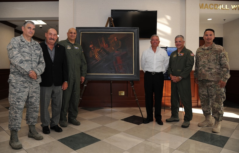 """Current and past members of the 919th Special Operations Wing stand beside the newly unveiled painting """"Ghost on the Highway"""" by Maj. Warren Neary during a ceremony May 23 at MacDill Air Force Base, Fla.  The painting marked the 25th anniversary of Operation Desert Storm and was unveiled with Gen. Raymond Thomas, commander of U.S. Special Operations Command, during the Retired Special Operations Senior Leader Conference.  (U.S. Air Force photo/Tech. Sgt. Peter Dean)"""