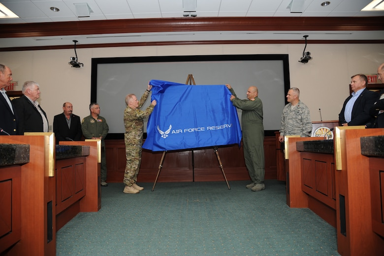"""Gen. Raymond Thomas III, commander of U.S. Special Operations Command, left, and Maj. Gen. Richard """"Beef"""" Haddad, vice commander of the Air Force Reserve Command, unveil a painting """"Ghost on the Highway"""" by Maj. Warren Neary during a ceremony May 23, 2016, at MacDill Air Force Base, Fla. The event marked the 25th anniversary of Operation Desert Storm during the Retired Special Operations Senior Leader Conference.  (U.S. Air Force photo/Tech. Sgt. Peter Dean)"""