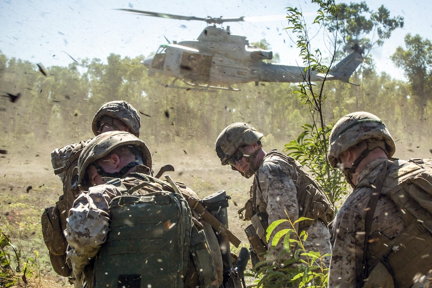 Marines endure debris from a UH-1Y Venom helicopter.