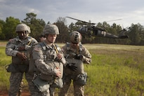 Army Chief Warrant Officer 5 Thomas Travis, right, a rotary wing advisor and pilot with U.S. Army Special Operations Aviation Command, and his son Pvt. Joshua Travis, center, a parachute rigger, prepare to board a UH-60 helicopter for a jump on St. Mere Eglise Drop Zone at Fort Bragg, N.C., during the Law Day Airborne Operation, May 5, 2016. Army photo by Spc. Rachel Diehm