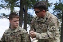 Army Chief Warrant Officer 5 Thomas Travis, right, a rotary wing advisor and pilot with U.S. Army Special Operations Aviation Command, and his son Pvt. Joshua Travis, a parachute rigger, discuss the procedures for their upcoming jump from a UH-60 helicopter at Fort Bragg, N.C., during the Law Day Airborne Operation, May 5, 2016. Army photo by Spc. Rachel Diehm