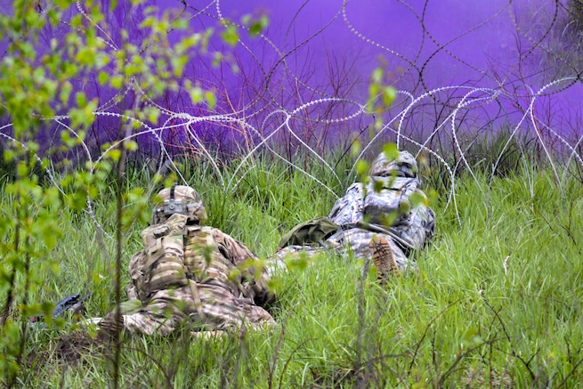 Soldiers assess a concertina wire obstacle under the cover of smoke and prepare to breach it using a bangalore torpedo during their Gunnery Table XII at Grafenwoehr Training Area, Germany, May 19, 2016. The soldiers are combat engineers assigned to the 3rd Infantry Division's 10th Engineer Battalion, 1st Armored Brigade Combat Team. Army photo by Maj. Randy Ready