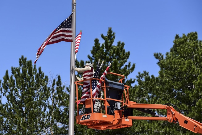 Air Force Staff Sgt. Steven Price attaches American flags to light poles on Stewart Avenue to commemorate Memorial Day at Peterson Air Force Base, Colo., May 23, 2016. Price is a structural journeyman assigned to the 21st Civil Engineer Squadron. He placed around 130 flags along the base's main roads before the holiday weekend. Air Force photo by Staff Sgt. Amber Grimm