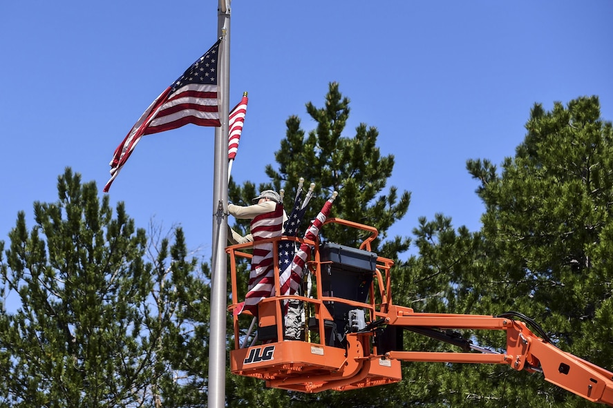 Air Force Staff Sgt. Steven Price attaching an American flag to a light pole.