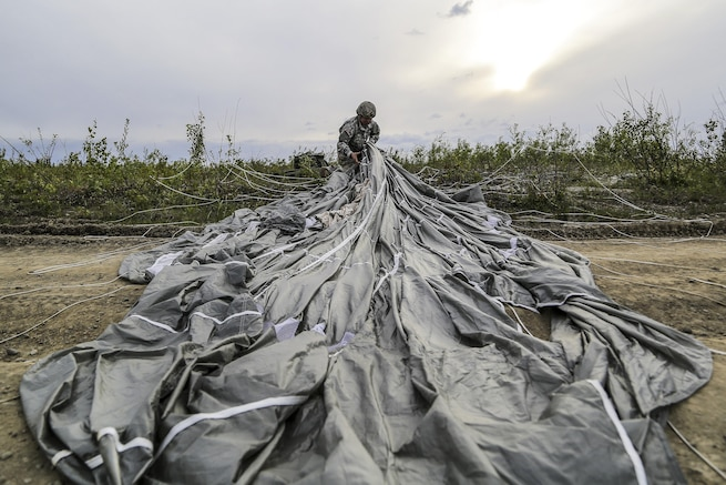 Army Spc. Donald Shingleton recovers his parachute during airborne and air transportability training at Joint Base Elmendorf-Richardson, Alaska, May 19, 2016. Shingleton is assigned to the 25th Infantry Division's 1st Battalion, 501st Parachute Infantry Regiment. Air Force photo by Alejandro Pena