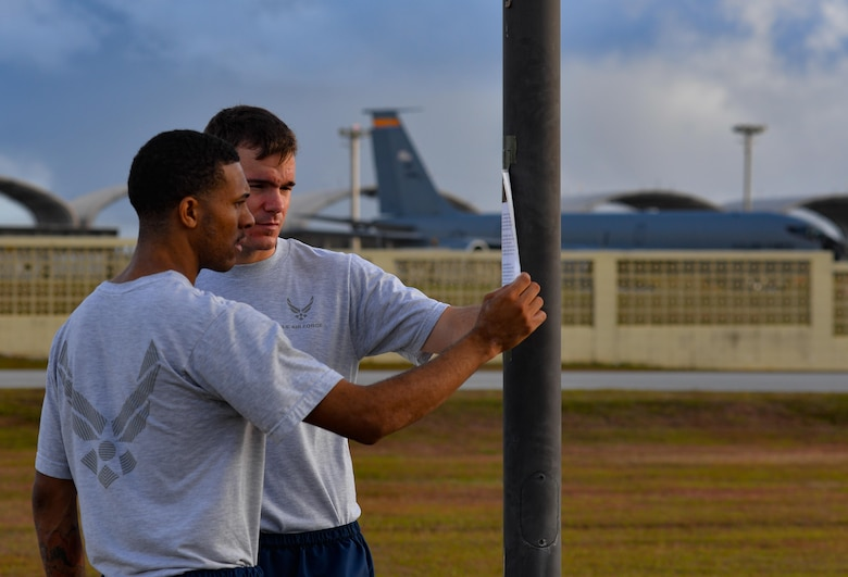 Senior Airman Damien Baker, left, and Airman 1st Class Albert White, 36th Comptroller Squadron financial services technicians,  read the story of a holocaust victim during a rememberance walk May 26, 2016, at Andersen Air Force Base, Guam. Andersen Airmen remembered the tragedy of the holocaust during an 11-hour vigil walk  past the names and stories of  individuals and families who suffered under the Nazi regime in Germany from 1933-1945. (U.S. Air Force photo by Staff Sgt. Alexander W. Riedel/Released)