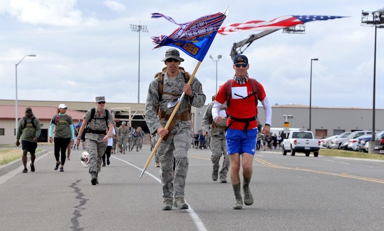 1st Lt. Derek Raska, 60th Civil Engineer Squadron deputy flight chief readiness and emergency management, carries his unit's guideon while participating in the Gold Star Families Ruck March at Travis Air Force Base, Calif., May 21, 2016. Approximately 200 service members participated in the sixth annual GSFRM, honoring the more than 45 Gold Star family members who were in attendance. (U.S. Air Force photo by Staff Sgt. Charles Rivezzo)