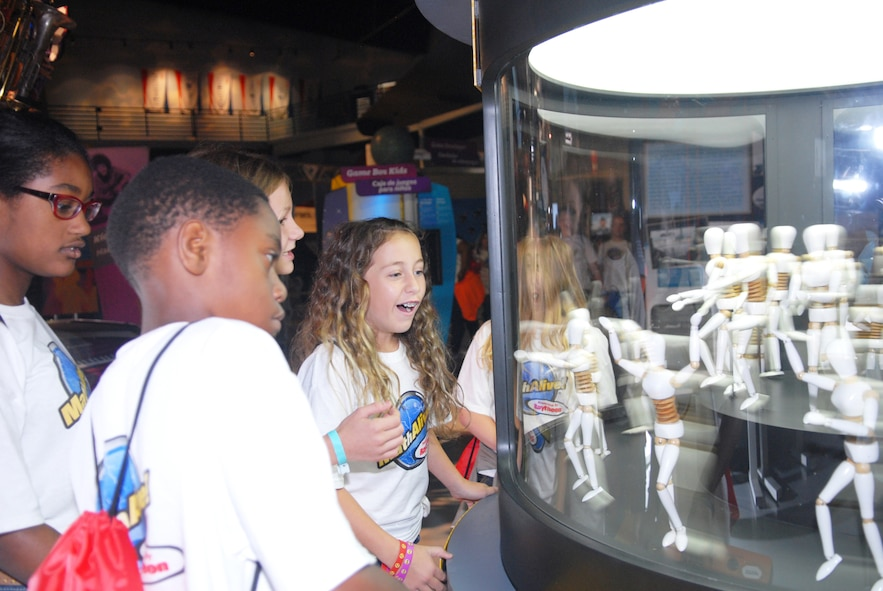 The fifth graders in Daughtry Elementary School in Jackson, Georgia, enjoy the Flicker Fusion interactive booth at the Museum of Aviation's Century of Flight Hangar. The students learned that when light flashes more than 24 flashes per second, it is too fast for the human eye to see. (U.S. Air Force photo by Misuzu Allen)