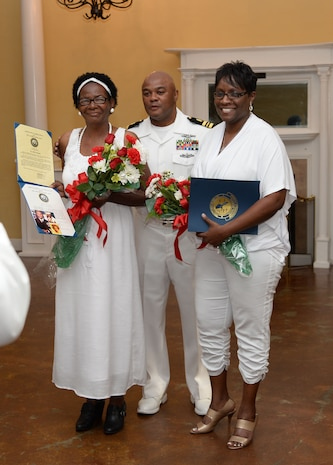 """Lt. Cmdr. Donald Mitchell, senior nurse executive, Naval Branch Health Clinic-Albany, aboard Marine Corps Logistics Base Albany, presents Certificates of Appreciation, American flags and roses to his mother, Alberta (left), his wife, Natalie (right), as well as other certificates to scores of other family members and friends during his retirement celebration. Mitchell retired after 30-years of active-duty service in the Navy at a """"fair winds"""" celebration held in his honor at the Orange Park Women's Club, Orange Park, Florida, May 14."""