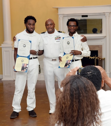 Lt. Cmdr. Donald Mitchell, senior nurse executive, Naval Branch Health Clinic-Albany, aboard Marine Corps Logistics Base Albany, presents Certificates of Appreciation to sons Jordon (left) and Davon (right) during his retirement celebration in Orange Park, Florida, May 14. Mitchell kicked-off his own retirement ceremony before the standing-room-only crowd of witnesses, donned in a sea of U.S. Navy summer uniforms and white civilian attire, who poured into the Orange Park Women's Club to celebrate the honoree. The retiree devoted 30 years of active-duty service in the U.S. Navy.