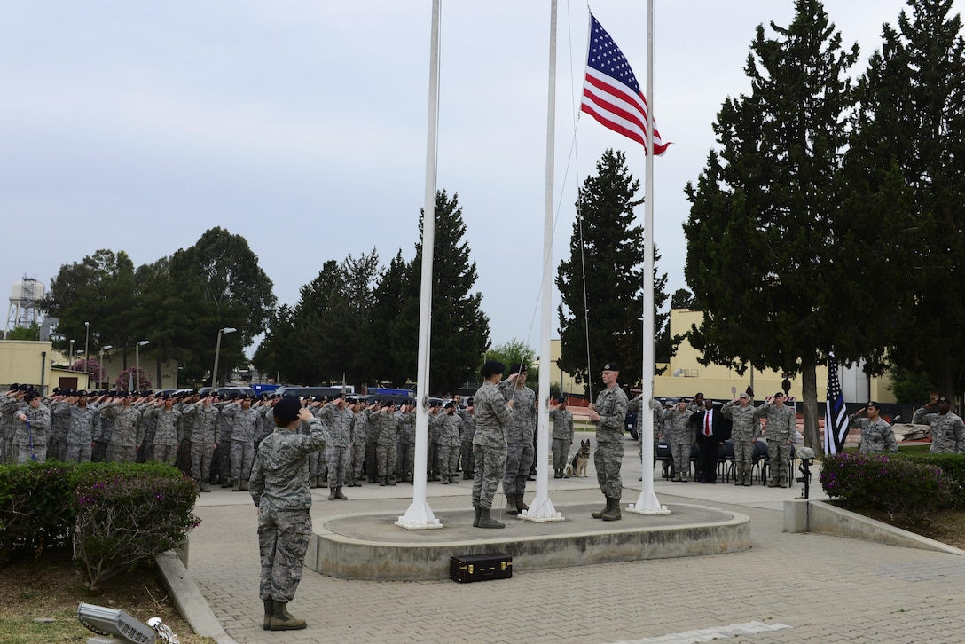 Members of the 39th Security Forces Squadron retrieve the U.S. flag during a National Police Week retreat ceremony May 15, 2016, at Incirlik Air Base, Turkey. National Police Week is dedicated to recognizing law enforcement officers who lost their lives in the line of duty. (U.S. Air Force photo by Staff Sgt. Caleb Pierce/Released)
