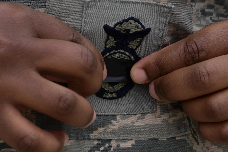 A 39th Security Forces Squadron defender, places a piece of black tape over their shield during a National Police Week retreat ceremony May 15, 2016, at Incirlik Air Base, Turkey. The black tape placed over the shield is a symbol of mourning fallen law enforcement officers. (U.S. Air Force photo by Staff Sgt. Caleb Pierce/Released)