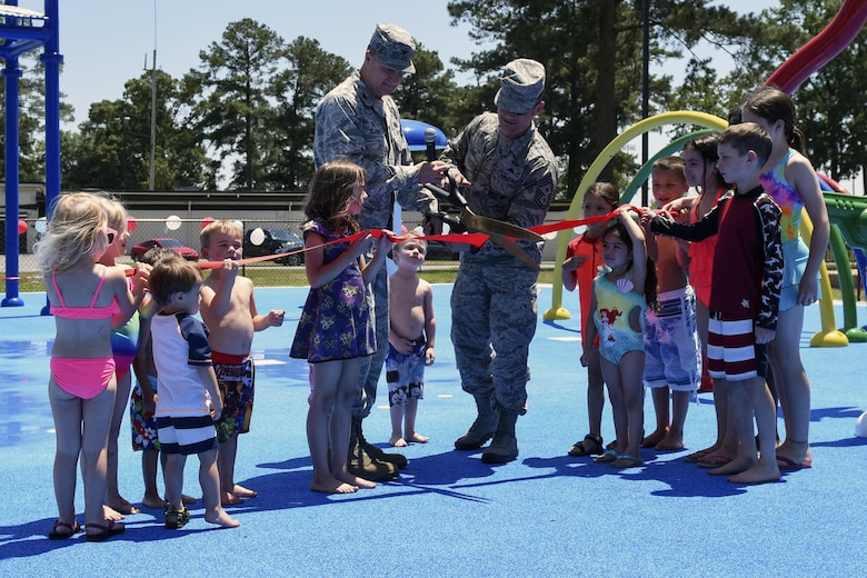 Col. Joseph Slavick (center left), 4th Mission Support Group commander, and Chief Master Sgt. Shane Wagner, 4th Fighter Wing command chief, cut the ribbon at the splash pad grand opening, May 24, 2016, at Seymour Johnson Air Force Base, North Carolina. The splash pad is open seven days a week from 9 a.m. to 9 p.m. through Labor Day weekend. (U.S. Air Force photo by Airman Shawna L. Keyes/Released)