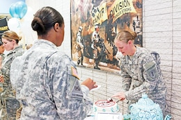 Capt. Alexandra DeAngeles, 299th Brigade Support Battalion, 2nd Armored Brigade Combat Team, 1st Infantry Division, slices a cake she and other members of her battalion made for the brigade's Sexual Assault Awareness Month cake competition that took place April 14 at Fort Riley's Barlow Theater.