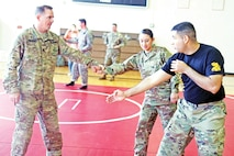 Staff Sgt. John D. Herrera, a native of Tampa, Florida, who works as the 1st Sustainment Brigade combatives instructor, explains a technique to two students during the brigades's Sexual Harassment and Assault Response and Prevention event April 14 at King Field House. The event is one of many the 1st Inf. Div. Sust. Bde. plans to conduct during the Army's SHARP Awareness month.