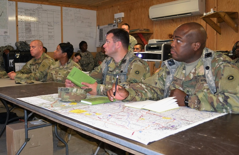 Col. Toni Glover, 650th Regional Support Group commanding officer, and her staff take a brief from Maj. Leopold Karanikolas, 314th Combat Sustainment Support Command commander, and his staff in the Intermediate Staging Base tactical operations center, during Joint Readiness Training Center, Fort Polk, exercises May 7, where units from the U.S. Army National Guard, Army Reserve and active-duty Army train together.