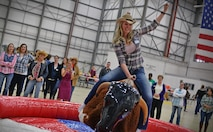 Lacey Keifer, 100th Civil Engineer Squadron spouse, rides the mechanical bull at the Spouse Appreciation Dinner May 24, 2016, on RAF Mildenhall, England. Spouses also had a barbecue dinner, and participated in line dancing and games. (U.S. Air Force photo by Senior Airman Christine Halan/Released)