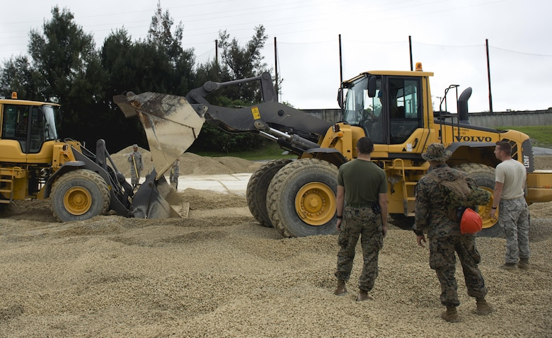 Marines fill a 50-foot crater during a two-day joint airfield damage repair exercise May 18, 2016, at Kadena Air Base, Japan. Airmen from the 18th Civil Engineer Squadron taught Marines and Navy Seabees how they repair damaged airfields. (U.S. Air Force photo/Senior Airman Omari Bernard)