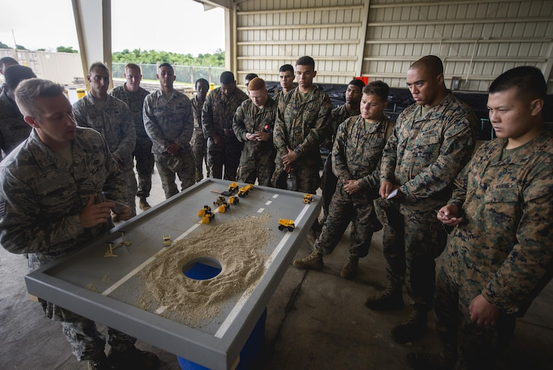 Airmen and Marines gather around a display model to go over a joint airfield damage repair exercise May 19, 2016, at Kadena Air Base, Japan. Airmen from the 18th Civil Engineer Squadron taught Marines and Navy Seabees how they repair damaged airfields. (U.S. Air Force photo/Senior Airman Omari Bernard)