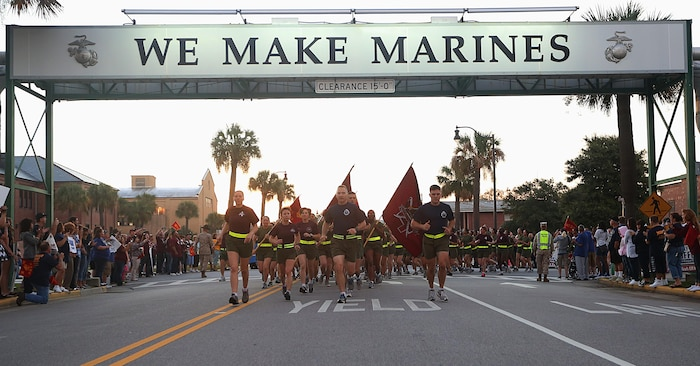"""Senior leaders from around Marine Corps Recruit Depot Parris Island lead the new Marines of Mike Company, 3rd Recruit Training Battalion, and November Company, 4th Recruit Training Battalion, under the """"We Make Marines"""" sign during a traditional motivational run Oct. 3, 2013, on MCRD Parris Island, S.C. The Marines sang cadence as they ran 2.3 miles past family and friends. Parris Island has been the site of Marine Corps recruit training since Nov. 1, 1915. Today, approximately 20,000 recruits come to MCRD Parris Island annually for the chance to become United States Marines by enduring 13 weeks of rigorous, transformative training. (Photo by Cpl. Caitlin Brink/Released)"""