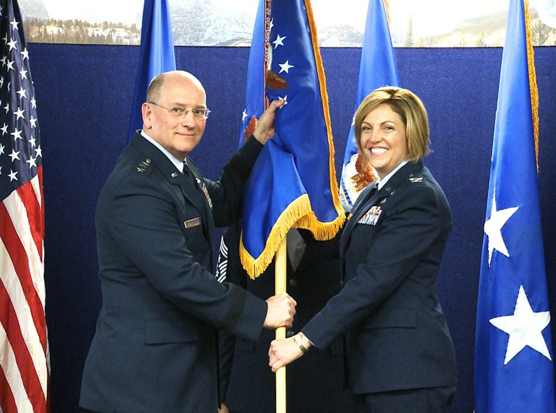 """Lt. Gen. James """"JJ"""" Jackson, chief of the Air Force Reserve and commander of the Air Force Reserve Command, passes the Air Reserve Personnel Center guidon to Col. Ellen M. Moore, incoming ARPC commander, during a change of command ceremony held May 26, 2016, on Buckley Air Force Base, Colo. Moore, the former Director of Manpower, Personnel and Services, Headquarters Air Force Reserve Command, Robins Air Force Base, Ga., assumed command of ARPC from Mahaney, who left the center to serve as the the Reserve Deputy Director, Director of Operations, Air Mobility Command, Scott Air Force Base, Ill. (U.S. Air Force photo/Quinn Jacobson)"""