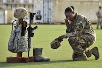Air Force Master Sgt. Tiffany Robinson kneels in front of a battlefield cross following a Memorial Day ceremony at Camp Lemonnier, Djibouti, May 26, 2014. Robinson is assigned to 449th Air Expeditionary Group. The cross was created with combat gear representing each of the five U.S. military branches to commemorate fallen service members. Navy photo by Petty Officer 1st Class Eric Dietrich