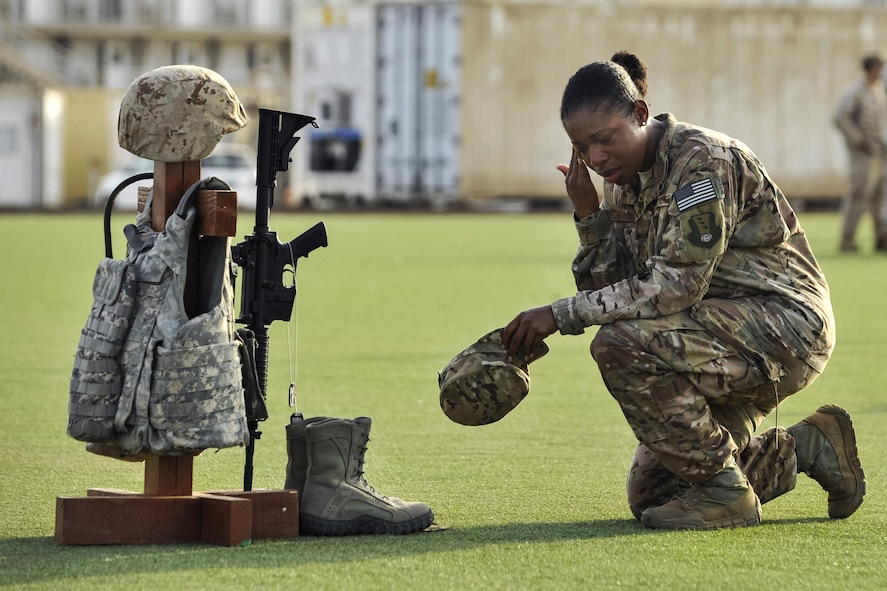 Air Force Master Sgt. Tiffany Robinson kneeling in front of a battlefield cross.