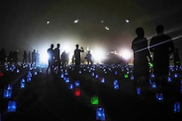 Soldiers walk across a field of 6,800 memorial lights, which represent  U.S. service members who have fallen in Iraq and Afghanistan, during a Memorial Day vigil on Camp Buehring, Kuwait, May 26, 2014. Army photo by Sgt. Marcus Fichtl