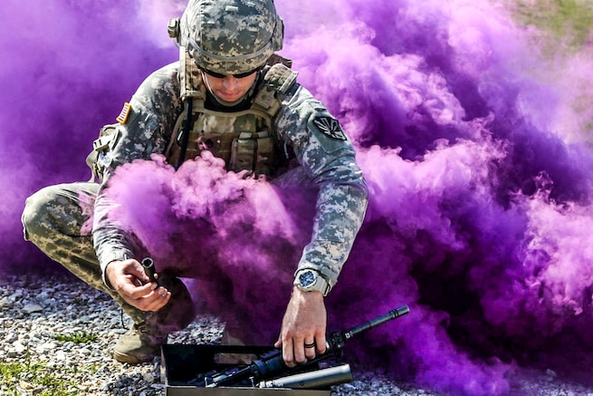 An Army flight medic assembles an M4 carbine as a thick cloud of smoke limits his visibility during the stress shoot portion of the Best Warrior Competition on Camp Bondsteel, Kosovo, May 21, 2016. Army photo by Staff Sgt. Thomas Duval