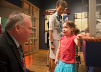 Joseph M. Judge, deputy director of Hampton Roads Naval Museum, explains an exhibit to a child who attended the launch of Blue Star Museums at the Hampton Roads Naval Museum in Norfolk, Va., May 26, 2016. Blue Star Museums is a collaboration among the National Endowment for the Arts, Blue Star Families, the Department of Defense and more than 2,000 museums across America to offer free admission to the nation's active duty military members and their families from Memorial Day through Labor Day. Navy photo by Petty Officer 3rd Class Amy M. Ressler