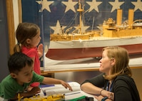 Laura Orr, deputy education director at Hampton Roads Naval Museum, teaches children about the exhibits after the launch of Blue Star Museums at the Hampton Roads Naval Museum, in Norfolk, Va., May 26, 2016. Blue Star Museums is a collaboration among the National Endowment for the Arts, Blue Star Families, the Department of Defense, and more than 2,000 museums across America to offer free admission to the nation's active duty military members and their families from Memorial Day through Labor Day. Navy photo by Petty Officer 3rd Class Amy M. Ressler
