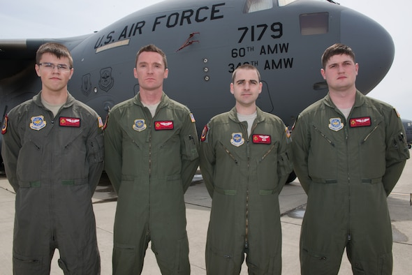 Pictured from left to right, Airman 1st Class Austen Copeland, Capt. Eric Rieboldt, Capt. Grant Hadley and Senior Airman Max Oldroyd, all assigned to the 21st Airlift Squadron, pose for a group picture on the flightline at Travis Air Force Base, Calif., April 26, 2016.  This aircrew evacuated injured Americans following the terrorist attacks in Brussels, Belgium. Not pictured but also part of the crew were 1st Lt. Justin Gross and Staff Sgt. Chase Decker. (U.S. Air Force photo by Louis Briscese)