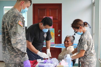 U.S. Army Spc. Tyler Novich, Honduran Dr. Wilmer Amador, and U.S. Army Maj. Margaret Novicio, Joint Task Force-Bravo Medical Element dental services, prepare to perform several tooth extractions on an elderly Nicaraguan woman during a Medical readiness Training Exercise in Alamikamba, Nicaragua, May 18, 2016. Several patients suffered from decaying teeth due to the bad water conditions and lack of preventive dental care in the area. Dental care is one of several services provided by the Medical Element, in cooperation with Nicaraguan Ministry of Health representatives. (U.S. Army photo by Maria Pinel)