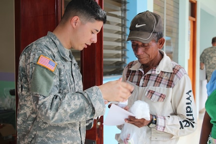 U.S. Army Cpl. Anthony Vargas, Joint Task Force-Bravo Joint Security Forces, facilitates translation between the pharmacy team and Nicaraguan nationals while handing out prescribed medications to patients during a Joint Task Force-Bravo-led Medical Readiness Training Exercise, May 19, 2016, in Alamikamba, Nicaragua. Free medication was provided for all those that visited the MEDRETE site after consultations with medical providers. (U.S. Army photo by Maria Pinel)