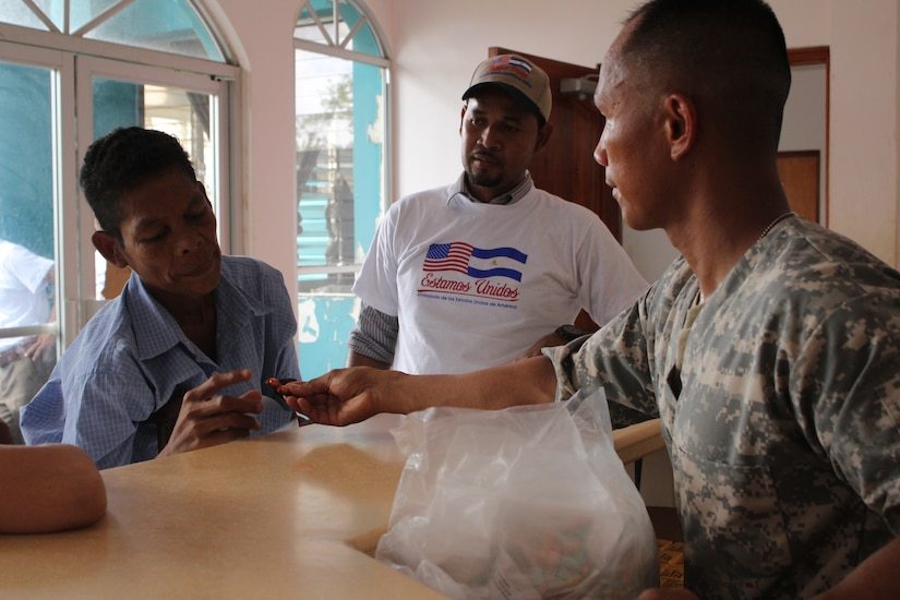U.S. Army Sgt. Jason Nisperos, Joint Task Force-Bravo preventive medicine officer in charge, hands out vitamins and deworming medication to a Nicaraguan man with the help of a Miskito translator during a Medical Readiness Training Exercise, 18 May 2016, in Alamikamba, Nicaragua. After receiving an initial health class, patients received a preventive care bag prior to visiting health care providers and pharmacy. The bag included vitamins for adults and children, deworming medication and soap. (U.S. Army photo by Maria Pinel)