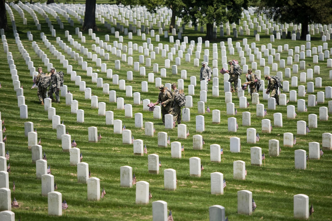 """Soldiers place American flags in front of headstones during """"Flags In"""" at Arlington National Cemetery in Arlington, Va., May 26, 2016. The soldiers are assigned to the 3rd U.S. Infantry Regiment, known as """"The Old Guard."""" Soldiers assigned to the regiment placed approximately 230,000 flags during the event, with each of the cemetery's headstones receiving a flag for the Memorial Day holiday. Army photo by Rachel Larue"""