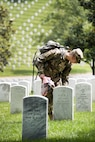 "Army Pfc. Jonathan Gretz places an American flag in front of a headstone during ""Flags In"" at Arlington National Cemetery in Arlington, Va., May 26, 2016. Gretz is assigned to the 3rd U.S. Infantry Regiment, known as ""The Old Guard."" Army photo by Rachel Larue"