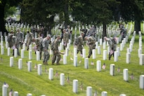 """Members of the 3rd U.S. Infantry Regiment, known as """"The Old Guard,"""" place American flags in front of headstones during """"Flags In"""" at Arlington National Cemetery in Arlington, Va., May 26, 2016, Army photo by Rachel Larue"""